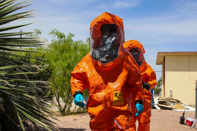 Two soldiers walk through desert terrain wearing orange hazmat suits.