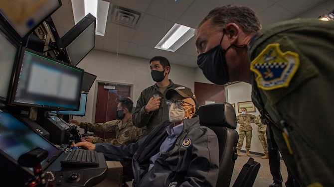 Two Air Force pilots in flight suits help an old man operate a flight simulator.