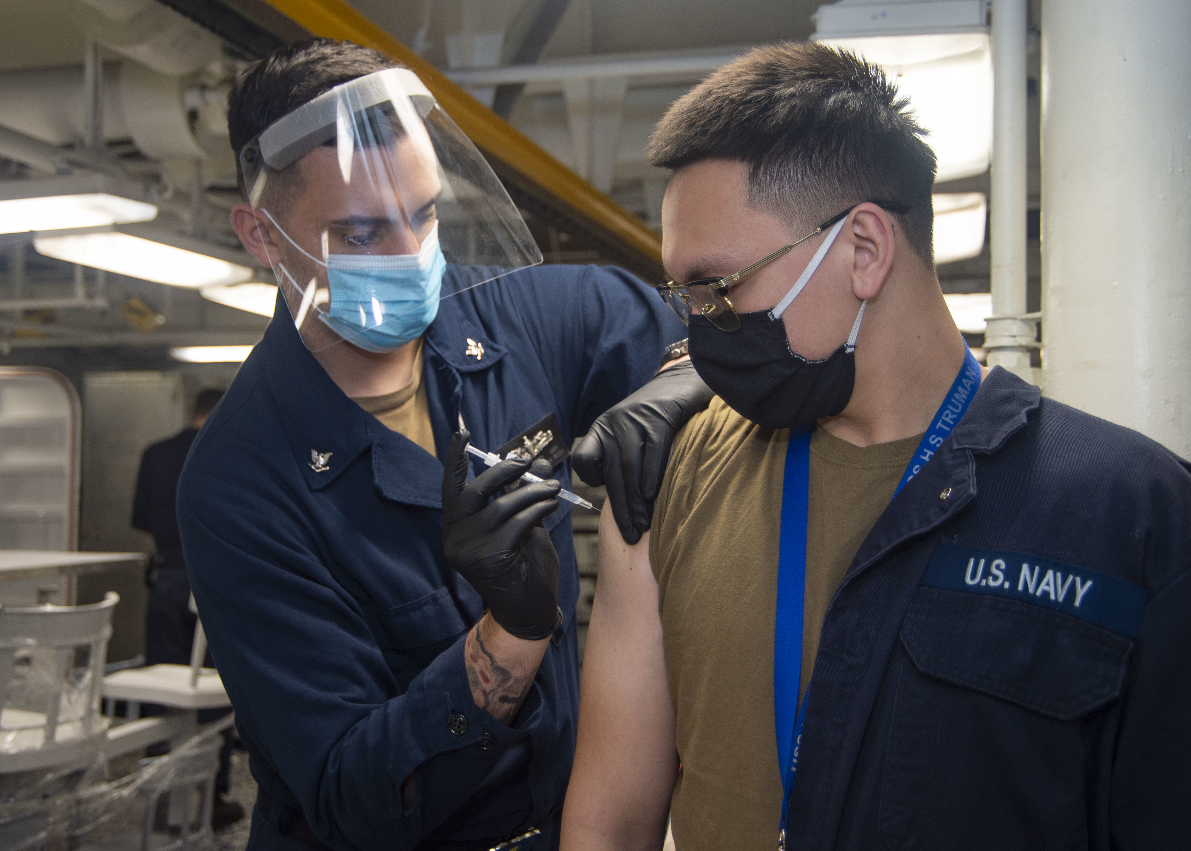 Hospital Corpsman 3rd Class Charles Connors, from Carmel, Indiana, left, administers a COVID-19 vaccine to Machinist's Mate Fireman Apprentice Christopher Musser, from Houston, on the forward mess decks aboard the Nimitz-class aircraft carrier USS Harry S. Truman (CVN 75).