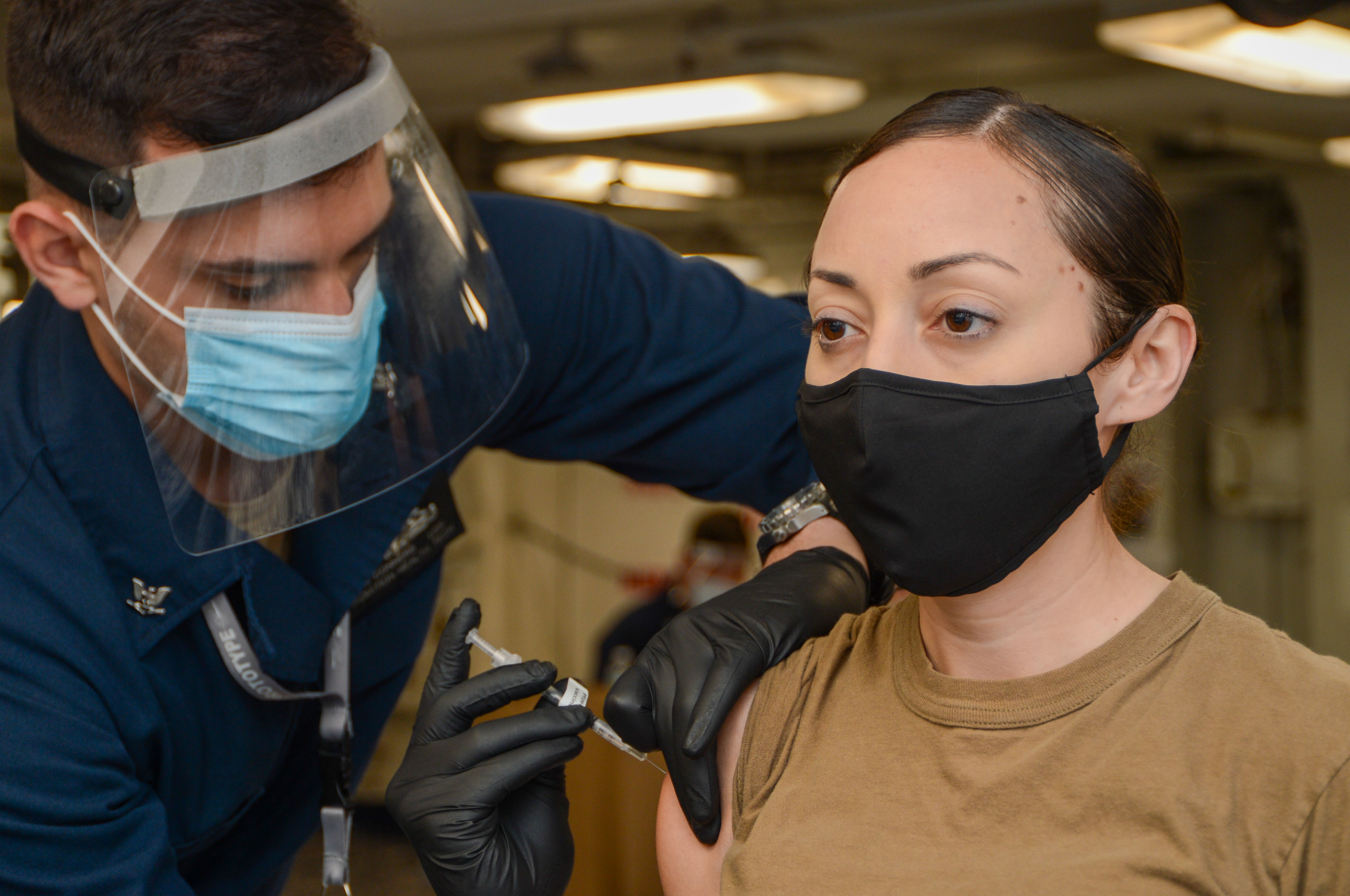 Hospital Corpsman 3rd Class Charles Conners, left, from Carmel, Indiana, administers a COVID-19 vaccine to Information Systems Technician 1st Class Krystina Garcia, from San Antonio, on the forward mess decks aboard the Nimitz-class aircraft carrier USS Harry S. Truman (CVN 75).