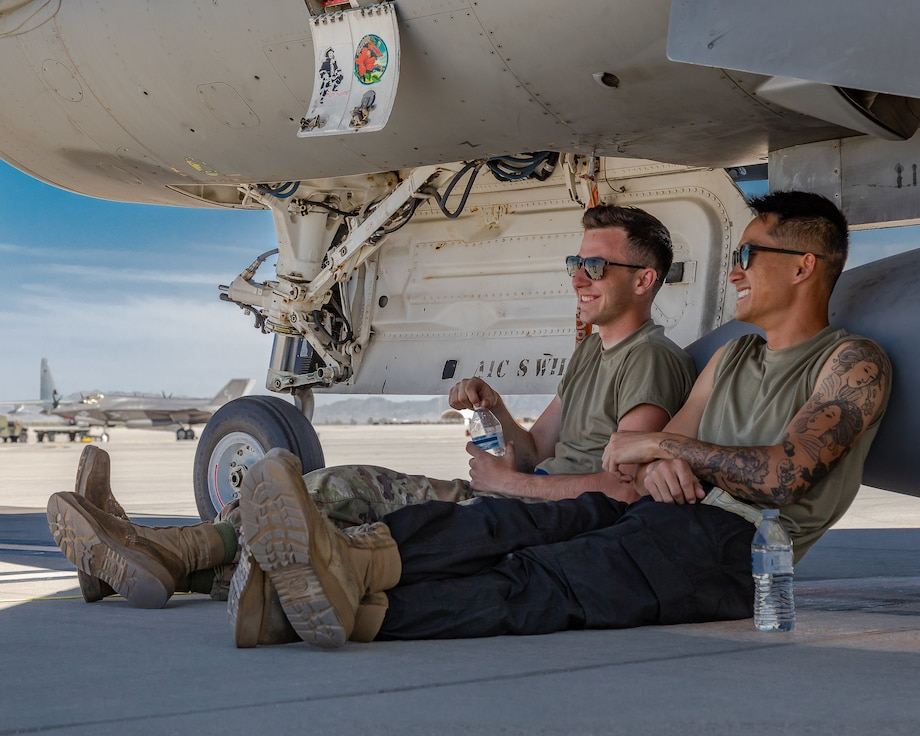 Two airmen sit and drink water underneath an F-16C+ Fighting Falcon.
