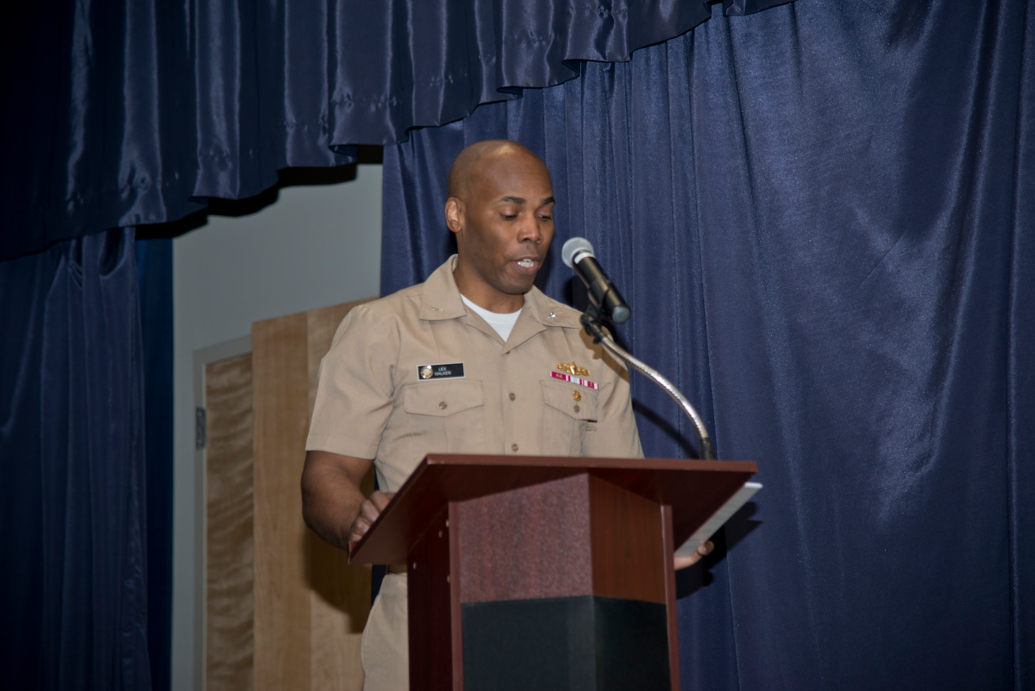 NEWPORT, R.I. (April 22, 2021) Capt. Alexis Walker, prospective commanding officer, Surface Warfare Schools Command (SWSC), reads his orders during the SWSC change of command ceremony at Naval Station (NAVSTA) Newport R.I., April 22, 2021. During the ceremony, Walker relieved Capt. Christopher Alexander as SWSC's commanding officer. (U.S. Navy photo by Mass Communication Specialist 2nd Class Derien C. Luce)