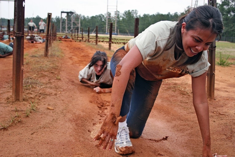 A smiling civilian begins to get up from a crawling position on a muddle obstacle course.