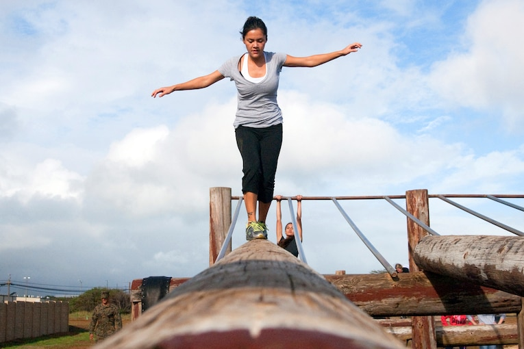 A person holds her arms out while walking on a raised horizontal log.