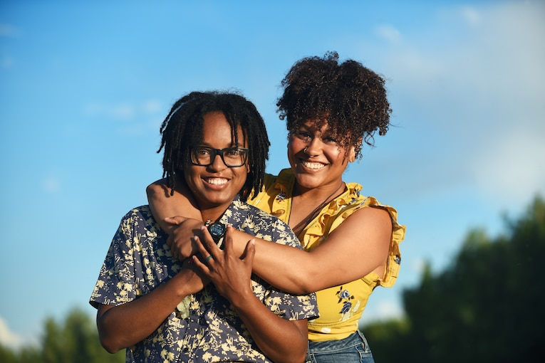 Two people in civilian clothes smile for a photo, one with her arms around the other.