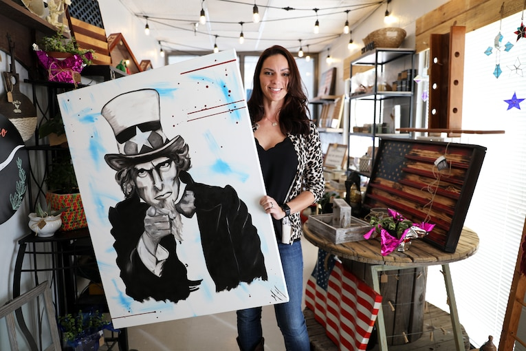 A civilian stands in a gift shop and holds up a drawing of Uncle Sam.