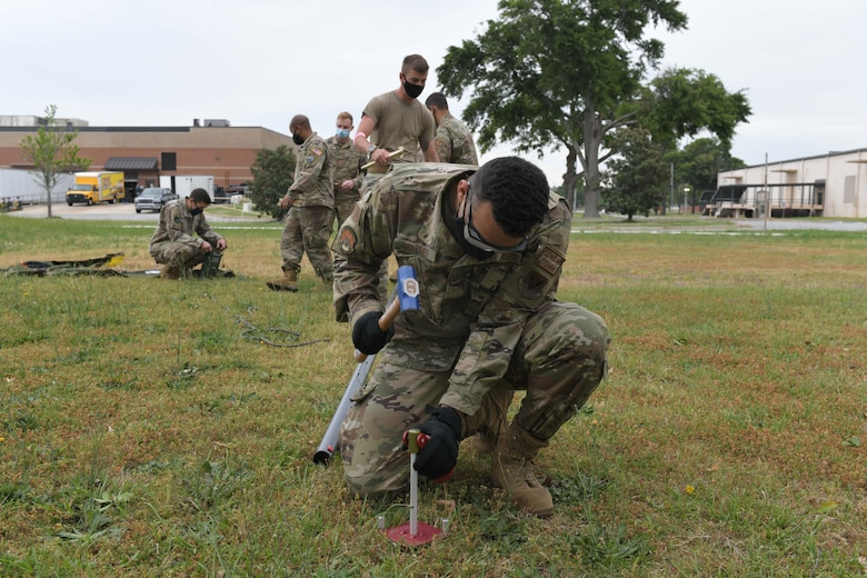 Photo shows Airman hammering spike into ground.