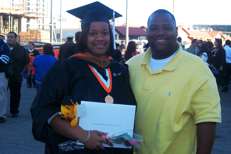 A man in civilian clothes stands for a photo outside with his wife, who is wearing a cap and gown.