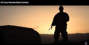 A military member is silhouetted against the sunset