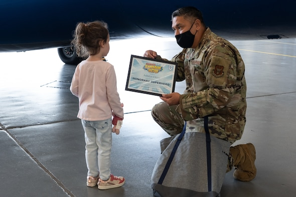 Kneeling Airman hands certificate to small child.