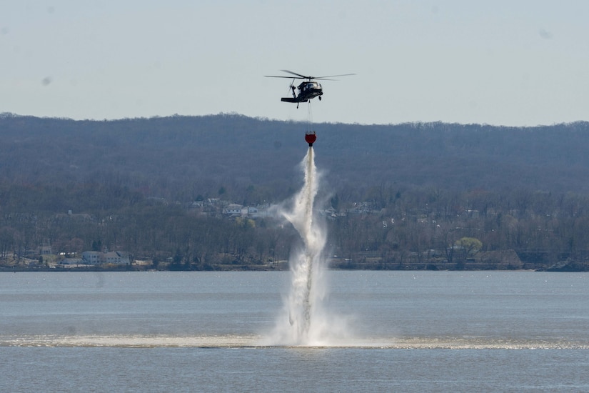 A helicopter dumps a bucket of water into a river.