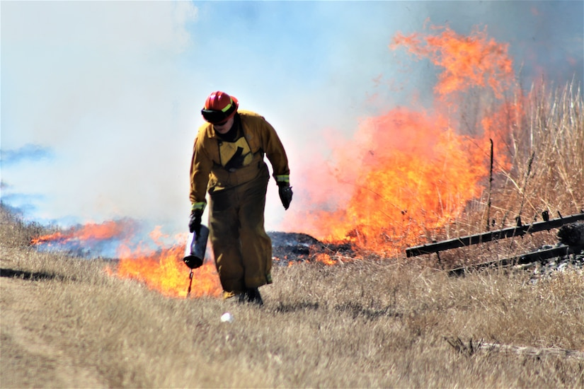 A person works with fire in a field.