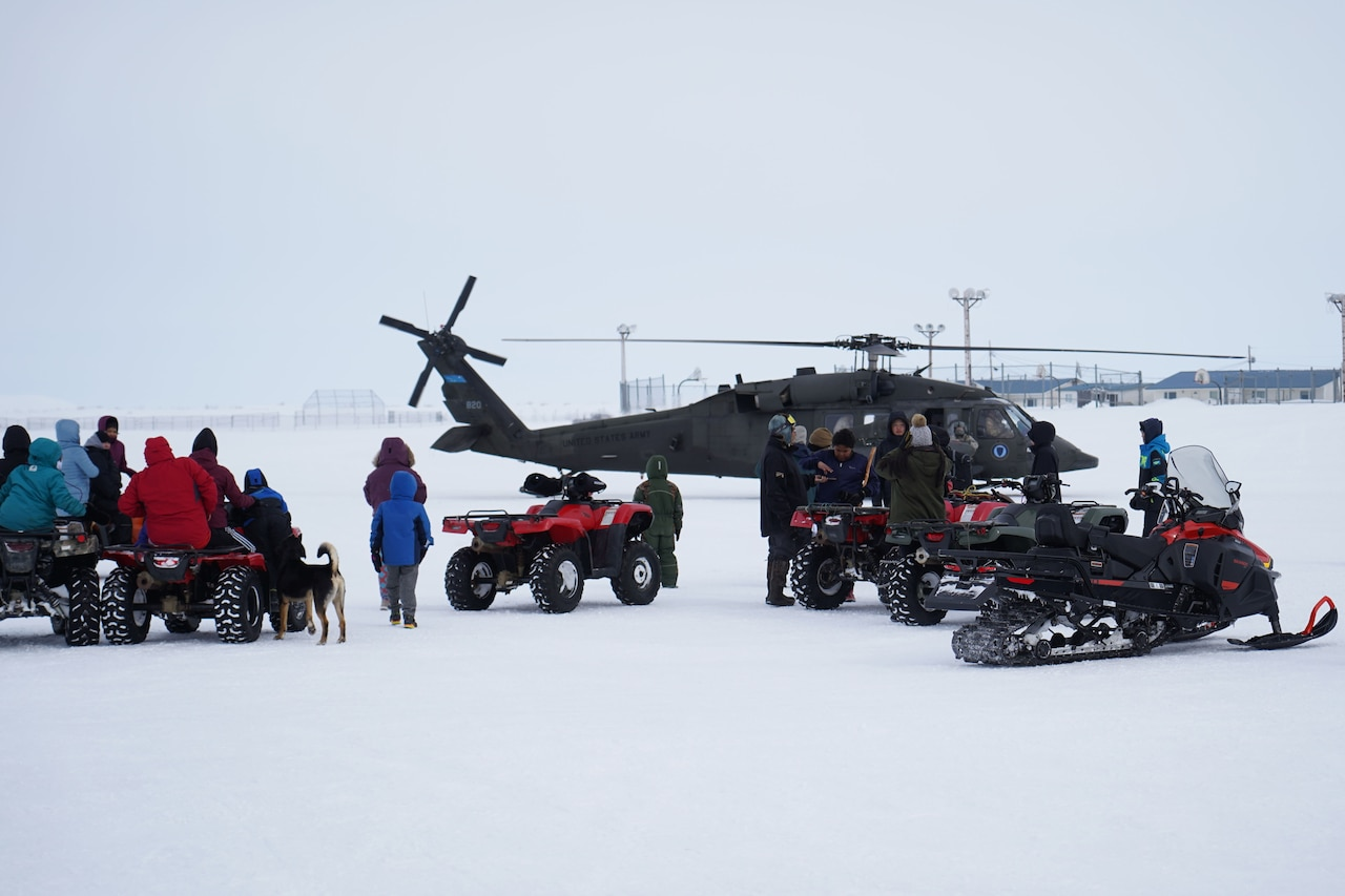 People mill about in the snow, There is a helicopter in the background.