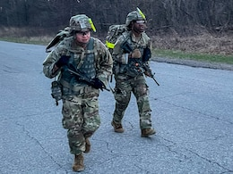 two soldiers march with weapons