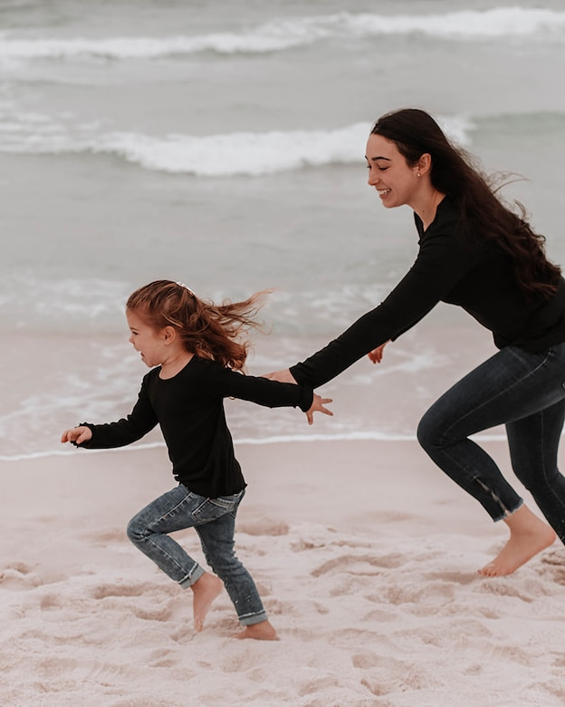 Woman and girl run on the beach