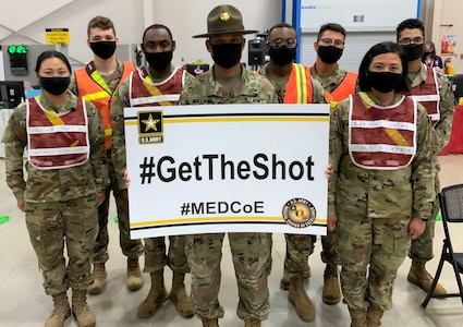 Staff Sgt. Marcus Williamson (center), a Drill Sergeant and 68J Medical Logistics Specialist assigned to Company C, 264th Medical Battalion, 32nd Medical Brigade, U.S. Army Medical Center of Excellence, or MEDCoE, pictured at the Brooke Army Medical Center's Joint Base San Antonio-Fort Sam Houston Vaccine site with 68C Practical Nursing Specialists augmenting BAMC personnel to administer the Pfizer BioNTech COVID-19 vaccine April 15.