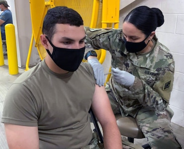 Pvt. Michael Giuffrida, a 68K medical laboratory specialist in training at the U.S. Army Medical Center of Excellence, or MEDCoE, is administered the first dose of the Pfizer BioNTech COVID-19 vaccine by Sgt. 1st Class Victoria Romero, MEDCoE 68W Combat Medic cadre augmenting staff, at the Brooke Army Medical Center's Joint Base San Antonio-Fort Sam Houston Vaccine site April 15.