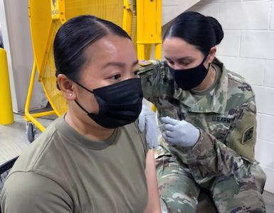 Spc. Hannah Le, 68K medical laboratory specialist in training at the U.S. Army Medical Center of Excellence, or MEDCoE, is administered the first dose of the Pfizer BioNTech COVID-19 vaccine by Sgt. 1st Class Victoria Romero, MEDCoE 68W Combat Medic cadre augmenting staff at the Brooke Army Medical Center's Joint Base San Antonio-Fort Sam Houston Vaccine site April 15.