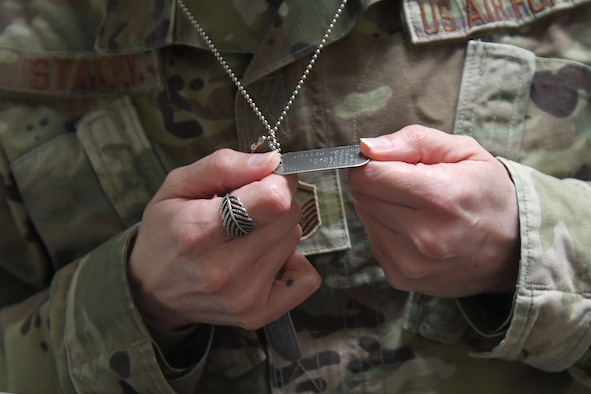 U.S. Air Force Master Sgt. Kristal Stacey, 81st Diagnostic and Therapeutics Squadron specialty imaging section chief, admires her new pair of dog tags inside the Taylor Logistics Center at Keesler Air Force Base, Mississippi, March 2, 2021. After the Air Force changed its policy to allow Native Americans to identify their Tribe or Nation on their identification tags, Stacey was the first in line to have her's made. (U.S. Air Force photo by Kemberly Groue)