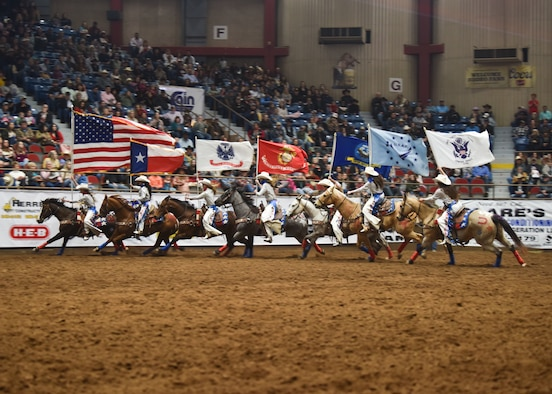 Rodeo participants ride around a rodeo ring holding U.S. service flags during Military Appreciation Night at the Foster Communications Coliseum, in San Angelo, Texas, April 21, 2021. The action was part of a long-standing tradition tied to this annual event. (U.S. Air Force photo by Staff Sgt. Seraiah Wolf)
