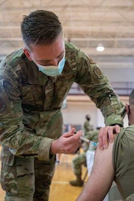 A man in a military uniform injects a syringe into the arm of a patient.
