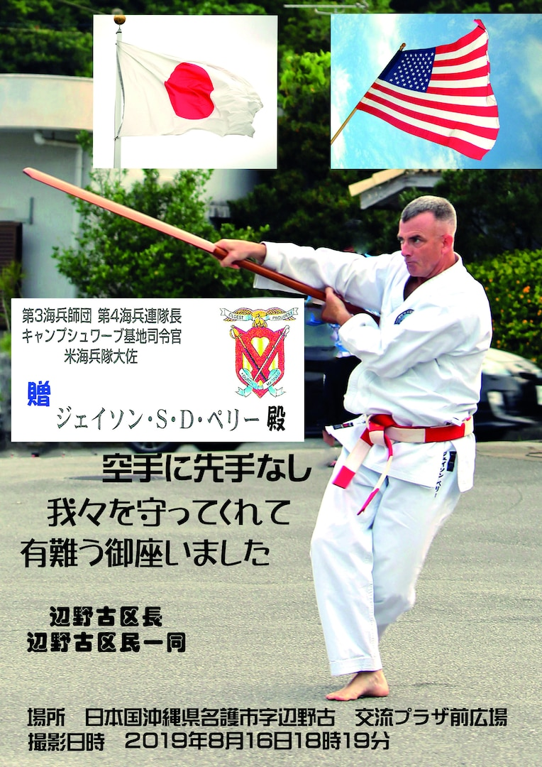 Col. Perry performs Kobudo Eku (boat oar) kata in Mura Odori. The residents of Henoko district presented this picture in the frame to Col. Perry to express their gratitude. PHOTO COURTESY BY ISAO MIYAGI