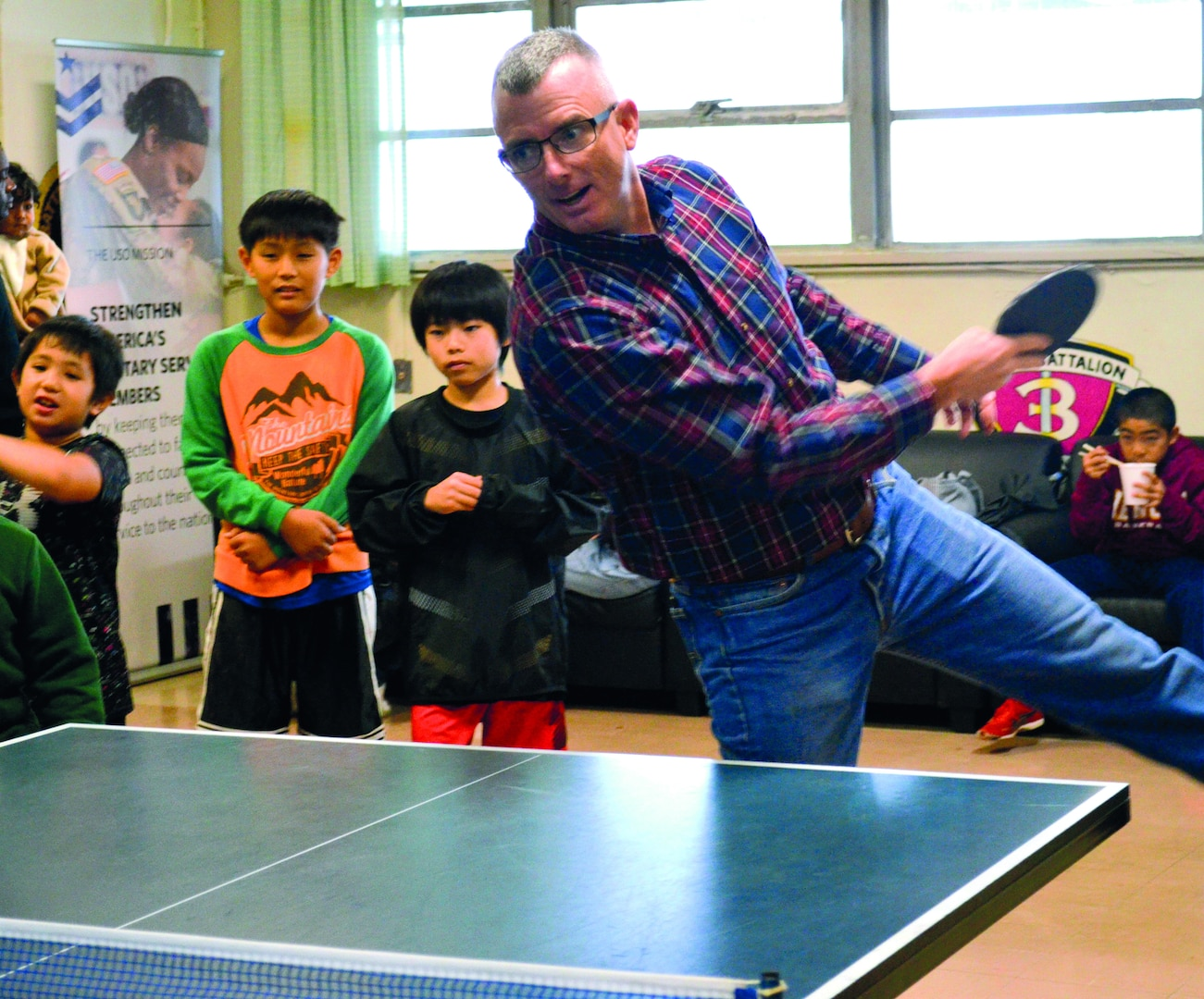 Col. Perry plays table tennis with a local child at the 38th Camp Schwab/USO Christmas Children's Day in Camp Schwab USO Dec. 7, 2019.