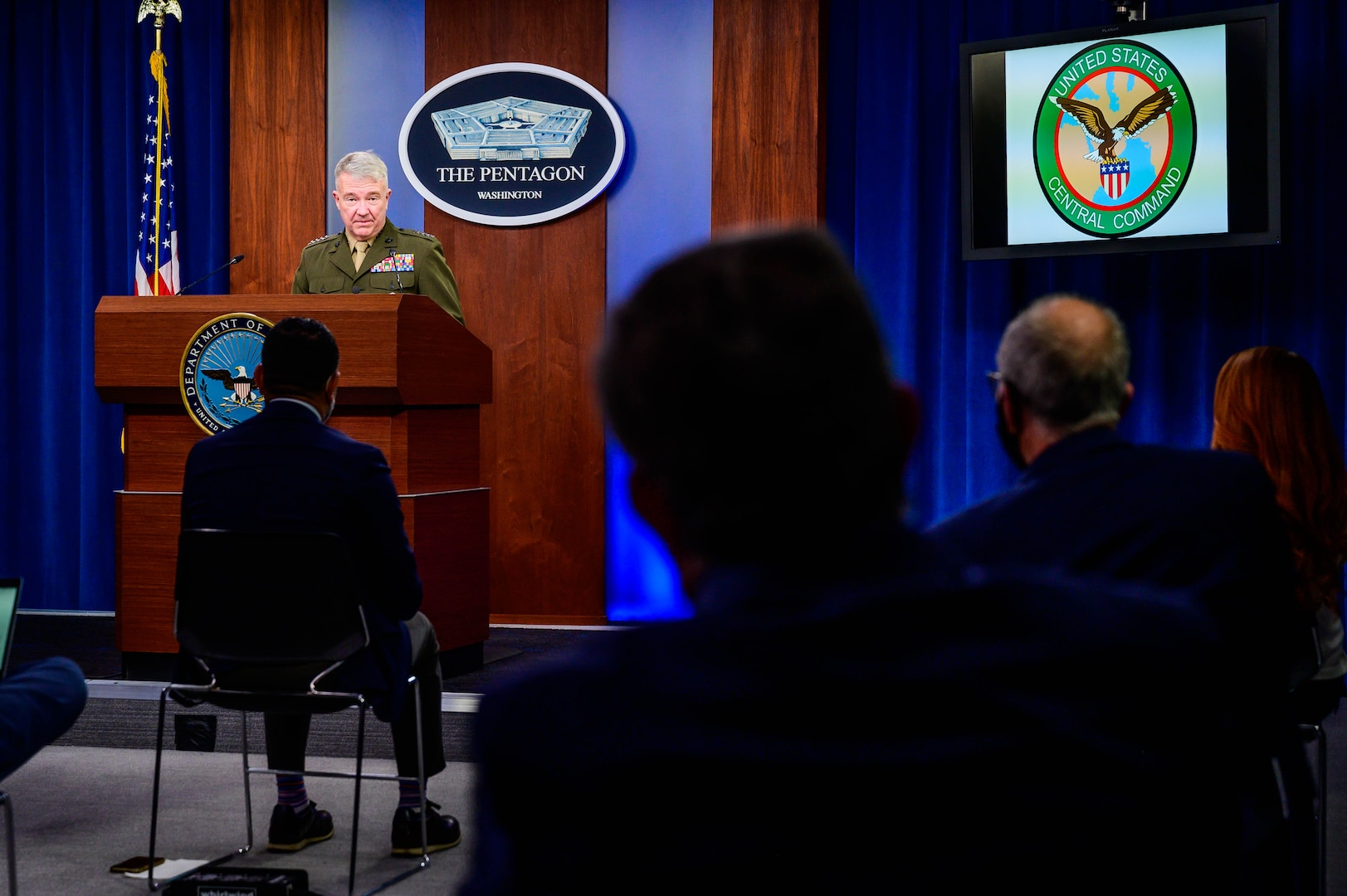 A man in a military dress uniform stands at a lectern. Behind him is a plaque indicating that he is at the Pentagon and seated reporters are silhouetted in the foreground.