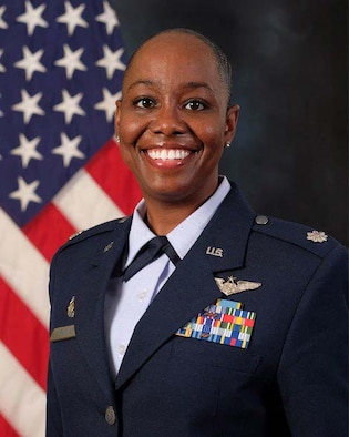 photo of Lt Col Mikita Brown standing in front of U.S. Flag