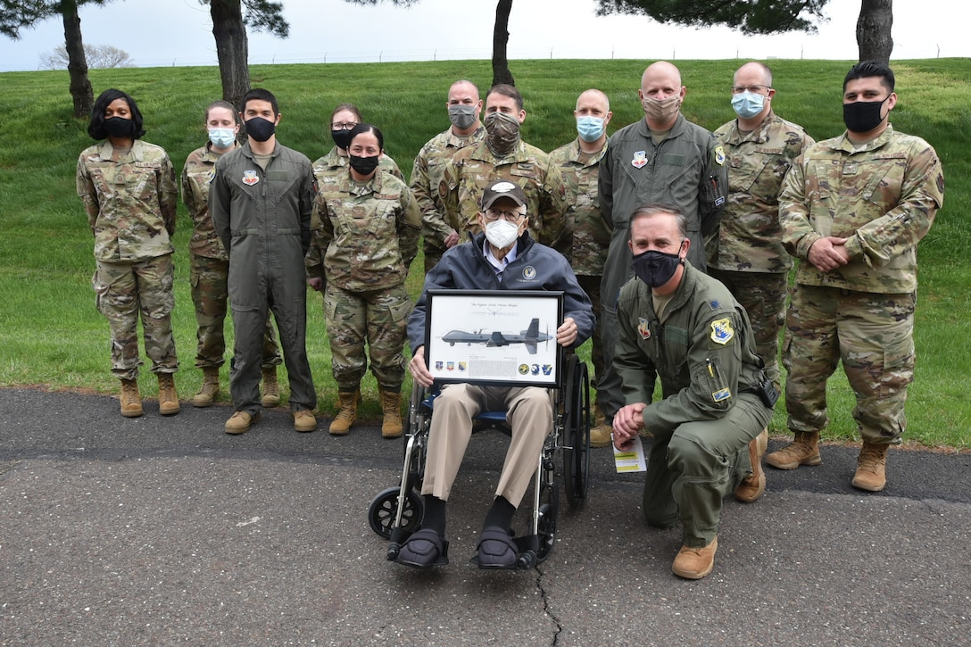 Air Force members pose for a photo with a World War II veteran sitting in a wheel chair holding a picture frame.