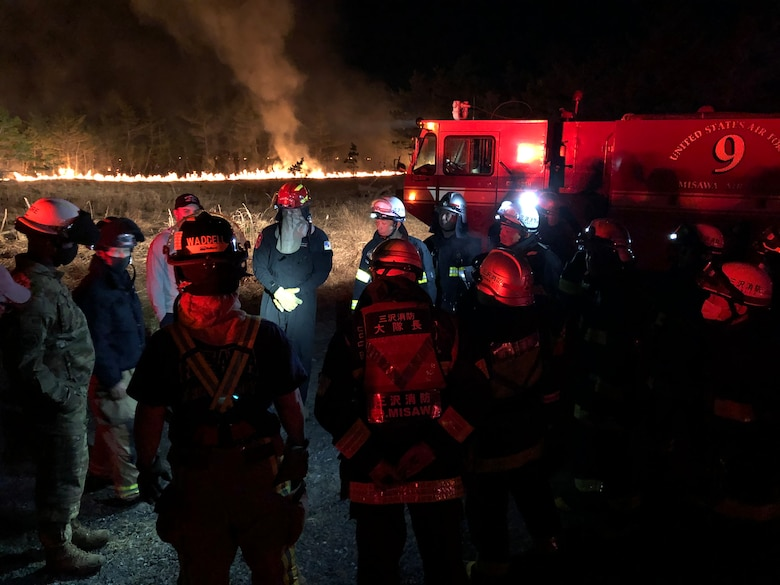 Fire crews stand near a fire truck and fire in a field
