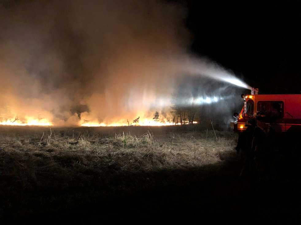 A fire truck sprays water to douse a fire in a field.