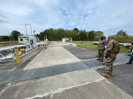 two people in military uniforms and one in civilian attire look at a truck fuel facility