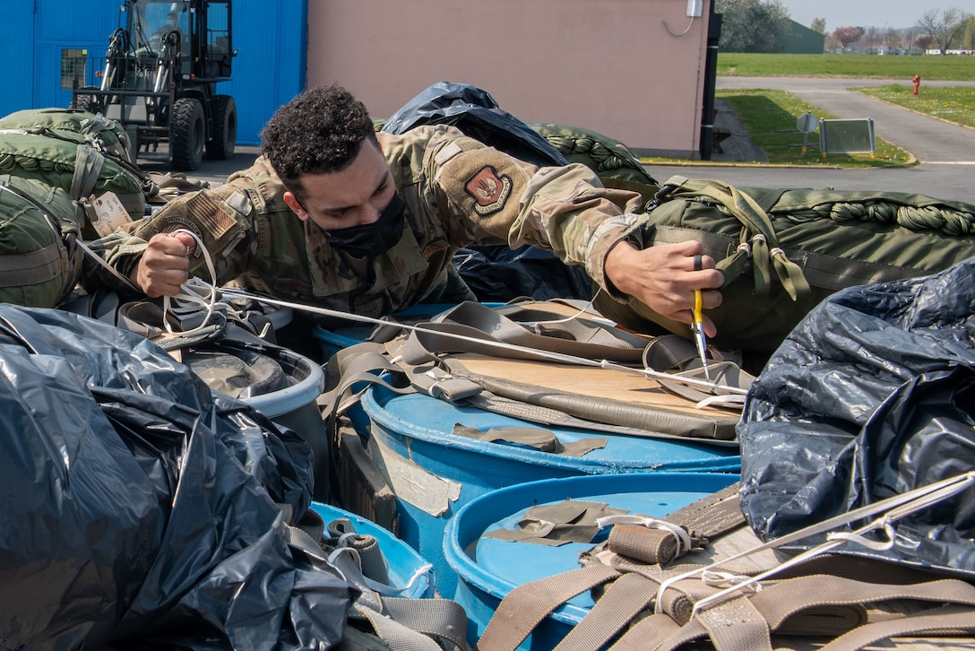 An Airman removes straps from a pallet