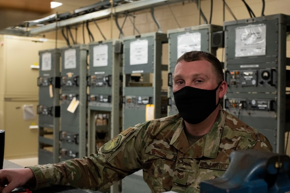 SSgt Richard Henley sits in front of radio equipment.