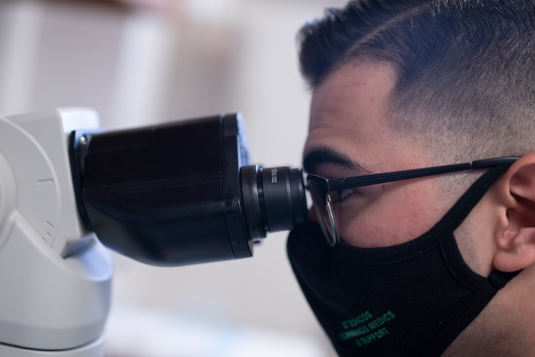 Senior Airman Charson Ashcraft, a laboratory technician assigned to the 27th Special Operations Healthcare Operations Squadron, looks through a microscope to perform a blood count at Cannon Air Force Base, N.M., April 12, 2021. Lab technicians perform duties such as blood counts in order to ensure the health and safety of the Air Force's number one priority, Airmen and their dependents. (U.S. Air Force photo by Airman 1st Class Christopher Storer)