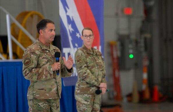 Two uniformed personnel address crowd