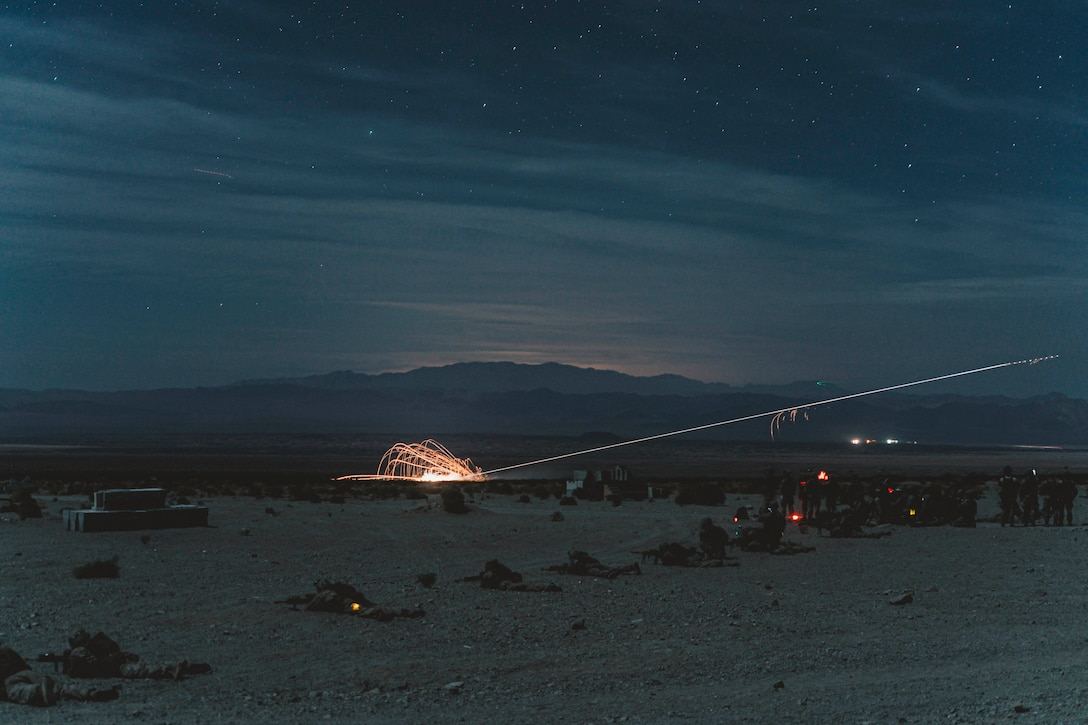 Marines lay on ground holding weapons in the desert while sparkly fly in the air nearby.