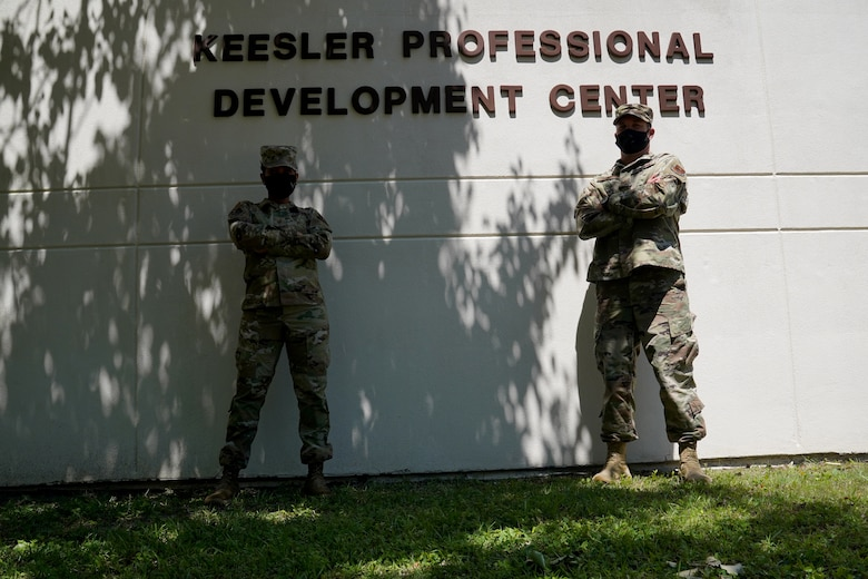 U.S. Air Force Master Sgt. Shenelka De Gannes, 81st Training Wing career assistance advisor, and Tech Sgt. Jason Repass, 81st TRW First-term Airman Course NCO in charge, pose for a photo in front of the Professional Development Center at Keesler Air Force Base, Mississippi, April 22, 2021. The PDC provides personal and professional development opportunities for service members. (U.S. Air Force photo by Senior Airman Seth Haddix)