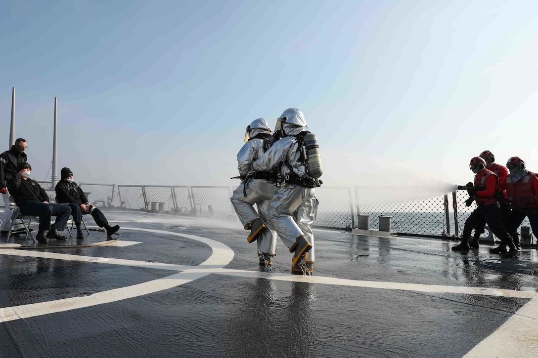 Sailors use a water hose to put out a simulated fire while other sailors wear fire suits on the flight deck of a ship at sea.