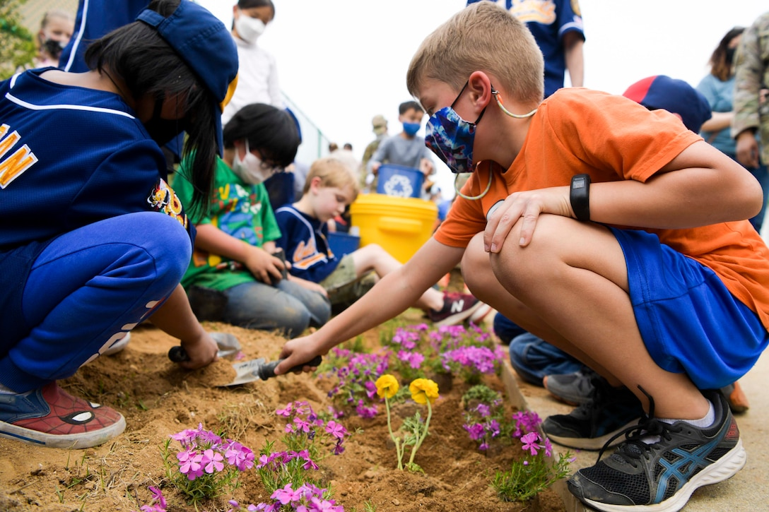 Children use small shovels to plant flowers in dirt.