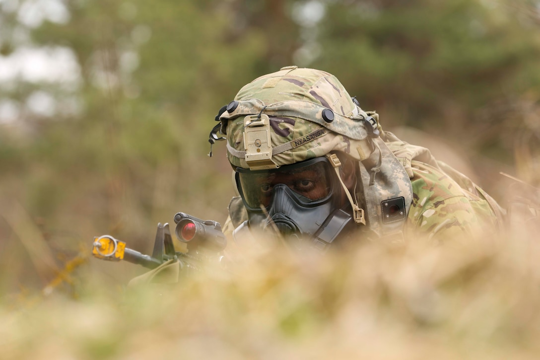 A soldier wearing a gas mask lies on the ground holding a weapon.