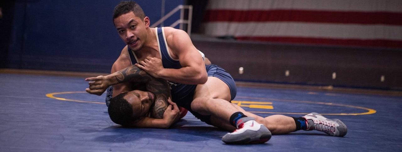 A wrestler holds another wrestler down on a mat.