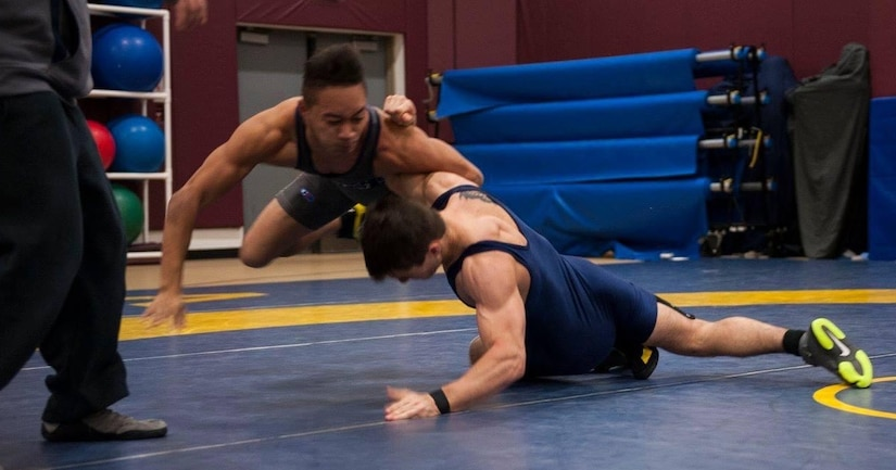 Two wrestlers compete on a mat.