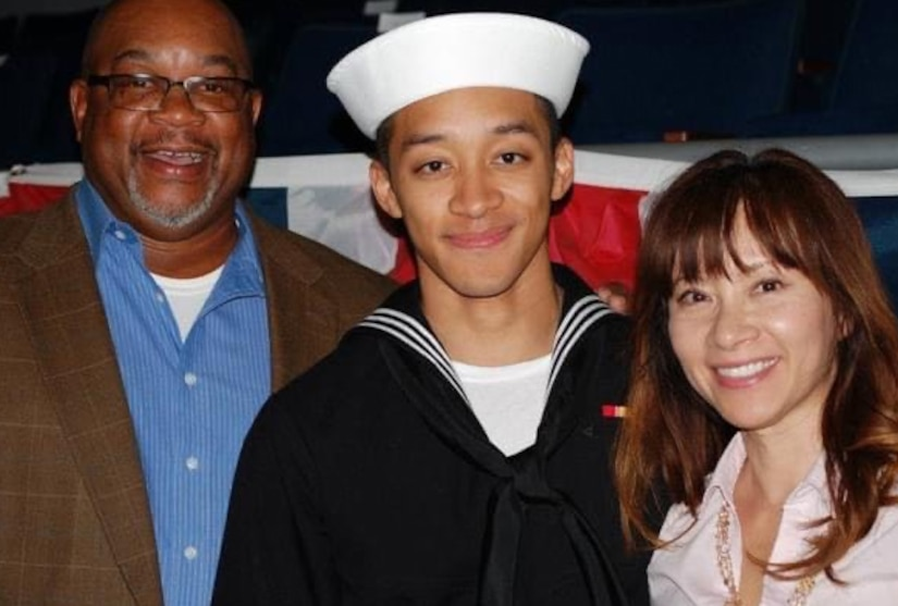 A young man in a military uniform stands between his parents and smiles for a photo.