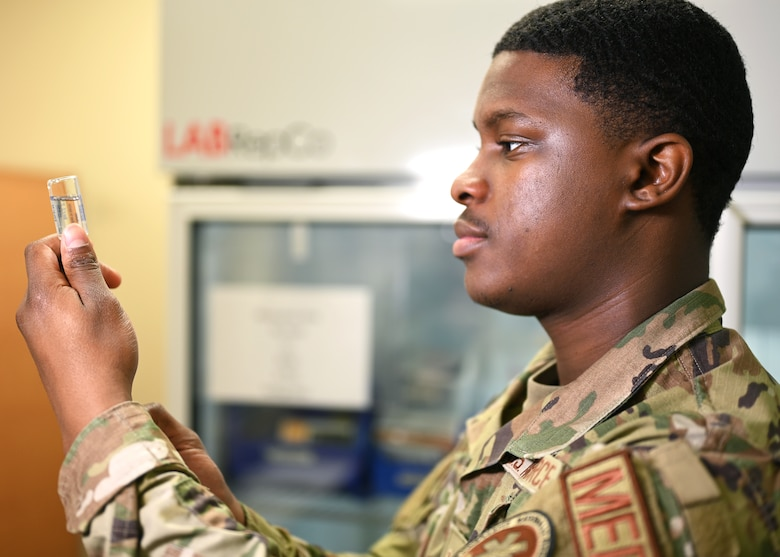 U.S. Air Force Senior Airman Micah Savage, 17th Medical Group immunizations technician, inspects a vial of saline during a demonstration of how vaccines are prepared for injection at the Ross Clinic on Goodfellow Air Force Base, Texas, April 19, 2021. Savage was entrusted as an immunizations technician to administer various vaccines to the base population. (U.S. Air Force photo by Airman 1st Class Michael Bowman)