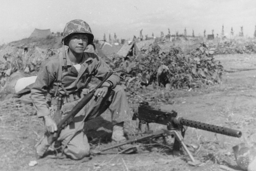 A Marine with a gun looks on.