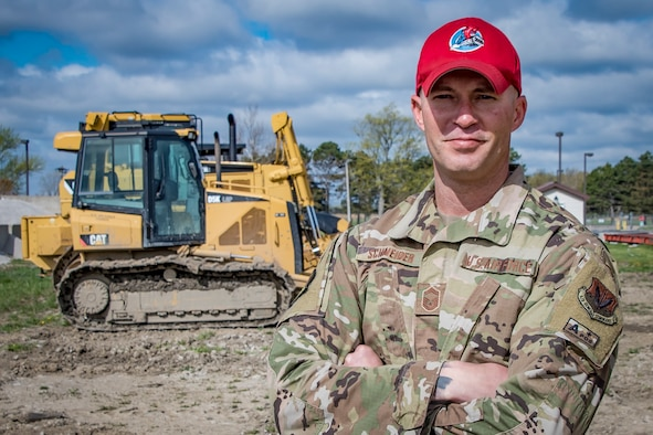 Senior Master Sgt. Mark Schneider, a pavement, maintenance and construction equipment superintendent, for the 200th RED HORSE stands in front of construction equipment.