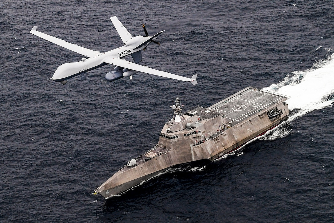 An unmanned aircraft flies over a Navy ship traveling in the sea.