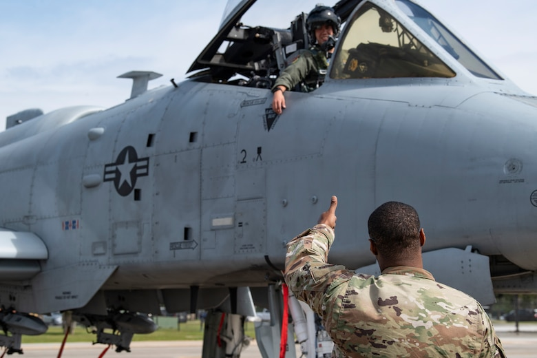 A photo of an Airman giving a thumbs up to a pilot